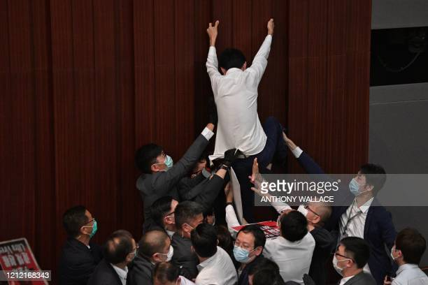 Pro-democracy lawmaker Eddie Chu Hoi-dick attempts to climb a wall in protest as security try to restrain him after pro-Beijing lawmaker Starry Lee...