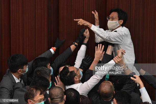 Pro-democracy lawmaker Eddie Chu Hoi-dick shouts at security trying to restrain him after pro-Beijing lawmaker Starry Lee sat in the chairpersons...