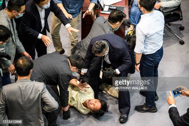 TOPSHOT Prodemocracy lawmaker Eddie Chu is surrounded by security as he and other prodemocracy lawmakers scuffle with proBeijing lawmakers at the...