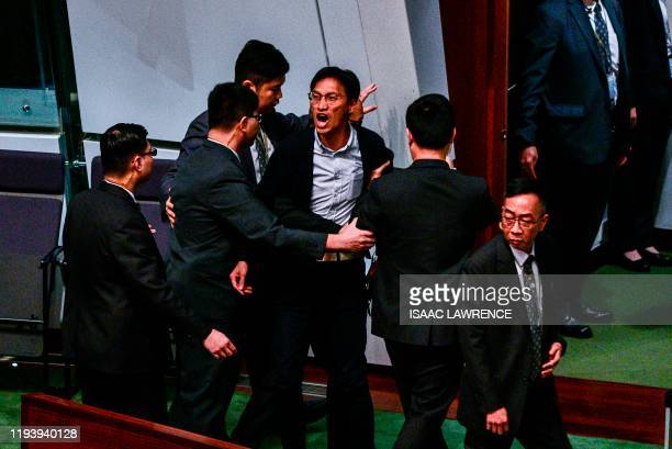 Pro-democracy lawmaker Eddie Chu yells while being removed from the legislative council while Hong Kongs Chief Executive Carrie Lam speaks during a...
