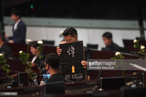 Prodemocracy lawmaker Gary Fan holds a placard as he and other prodemocracy lawmakers hold five minutes of silence in the Legislative Council in Hong...