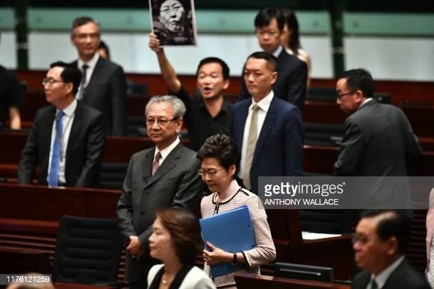 Pro-democracy lawmaker holds up a placard in protest as Hong Kong's Chief Executive Carrie Lam walks into the chamber to give her annual policy...