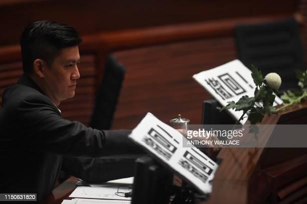 Prodemocracy lawmaker Jeremy Tam adjusts a white flower as he and other prodemocracy lawmakers hold five minutes of silence in the Legislative...