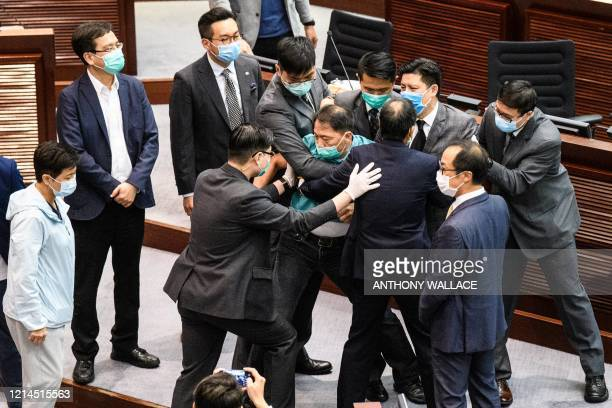 TOPSHOT Prodemocracy lawmaker Wu Chiwai is escorted by security out of the Legislative Council after prodemocracy lawmakers disrupted a House...