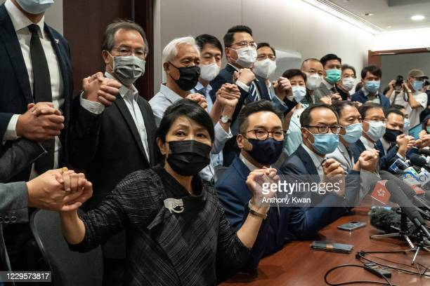 Pro-democracy lawmakers join hands during a press conference at the Legislative Council Building on November 11, 2020 in Hong Kong, China. Hong...
