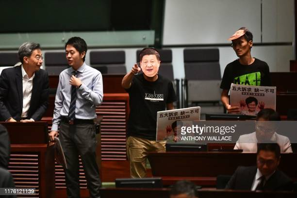 Pro-democracy lawmakers wearing masks with the image of China's President Xi Jinping disrupt proceedings during the annual policy address of Hong...
