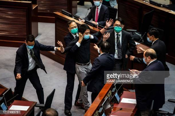 Pro-democracy legislator Ted Hui is removed by security guards after throwing a jar containing a four-smelling liquid onto the floor during a debate...