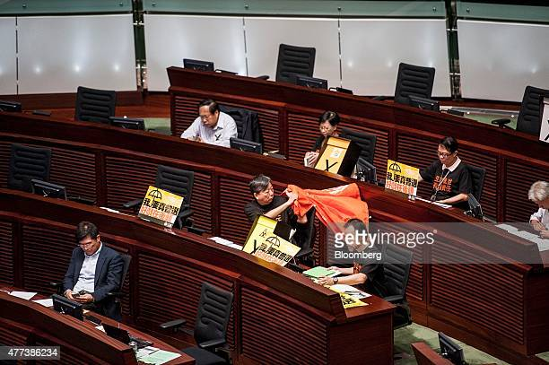 Prodemocracy legislators sit next to protest signs during a session in the chamber of the Legislative Council in Hong Kong China on Wednesday June 17...