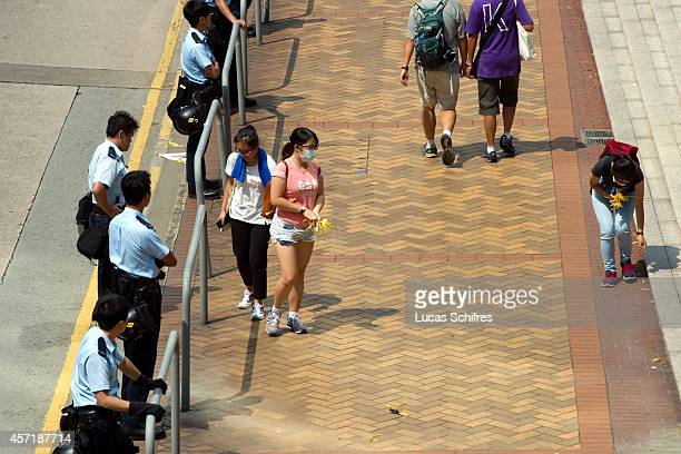 Pro-democracy 'Occupy Central' female protesters collect and dispose of yellow ribbons, symbols of the 'Umbrella revolution', to clean up after their...