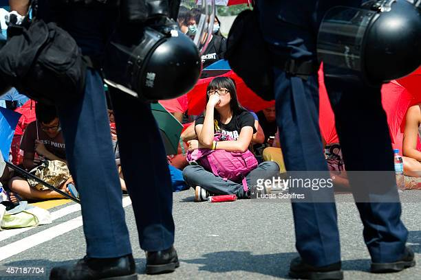 Pro-democracy 'Occupy Central' protester participates in a sit-in facing armed police who just removed barricades in Admirality on October 14, 2014...