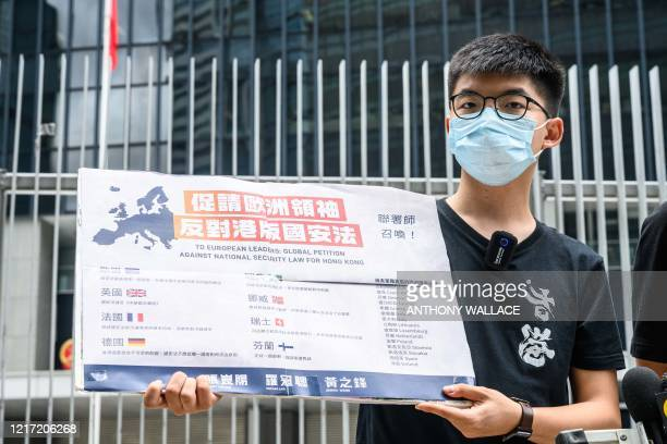Pro-democracy party Demosisto member Joshua Wong holds a placard urging European leaders to act against a national security law during a press...