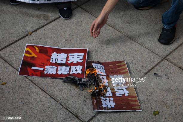 Pro-democracy prostesters burn posters during a rally against a new national security law in Hong Kong on July 1 on the 23rd anniversary of the...