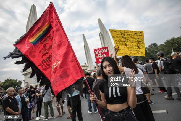 Pro-democracy protester and also student gives the three finger salute while holding an LGBT flag in front of Democracy Monument during an...