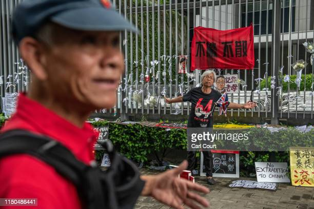 A prodemocracy protester argues with a man after he placed 'Quotations from Chairman Mao Tsetung' books next to protest posters outside the...