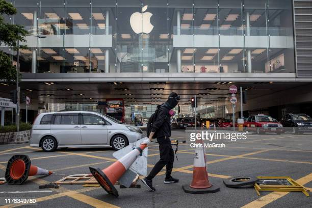 A prodemocracy protester blocks a road outside the Apple store during clashes with police on October 01 2019 in Hong Kong China Prodemocracy...