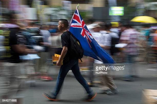 ProDemocracy protester carries the Hong Kong colonial flag in Hong Kong July 1 2016 Pro Democracy protesters march as the city marks the 19th...