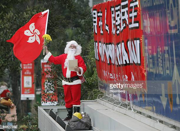 A prodemocracy protester dressed as Santa Claus waves a Hong Kong flag and a copy of proposed legislation next to a banner he erected calling for...