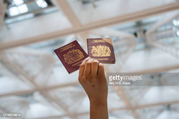 A prodemocracy protester holds a British passport during a Lunch With You rally on June 1 2020 in Hong Kong China