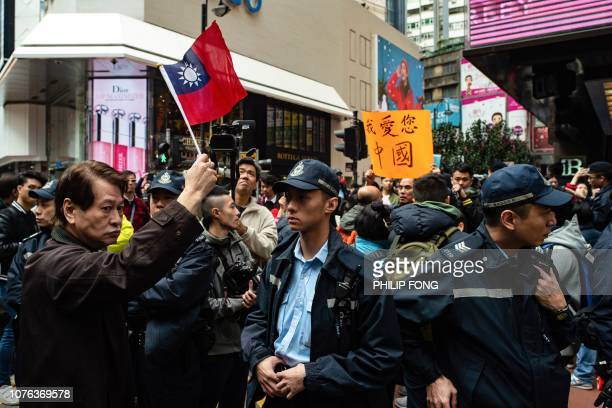 A prodemocracy protester holds a Taiwanese flag as a proBeijing supporter holds a placard reading 'I love you China' during the annual New Year's Day...