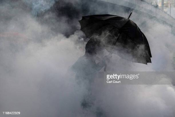 A prodemocracy protester holds an umbrella as he moves through teargas during clashes at the Central Government Offices on September 15 2019 in Hong...