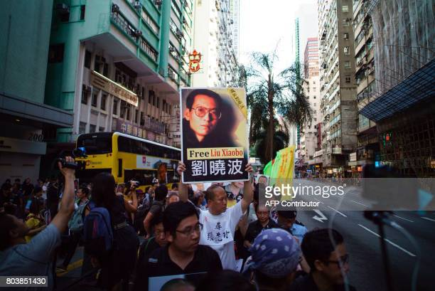 A prodemocracy protester holds up a placard with a picture of Chinese Nobel laureate Liu Xiaobo on it during a demonstration in Hong Kong on June 30...