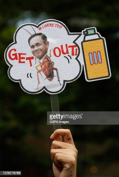 Pro-democracy protester holds up a placard with an image of the prime minister reading 'GET OUT' during the demonstration at Ratchaprasong...