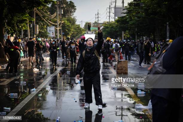 Pro-democracy protester holds up a three finger salute after police fired tear gas and water canon to try and disperse them outside Parliament on...