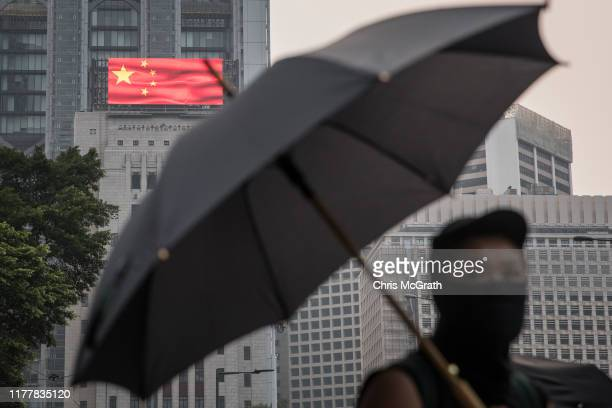 A prodemocracy protester is seen in front of a building displaying the Chinese National flag during clashes with police after a march on September 29...