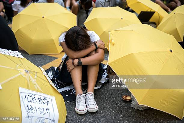 A prodemocracy protester rests among yellow umbrellas symbols of the prodemocracy movement in Hong Kong during a faceoff with police near the central...