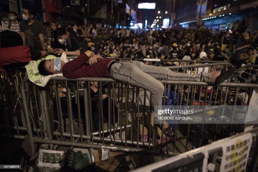A pro-democracy protester sleeps atop a barricade in the Mongkok district of Hong Kong on October 19, 2014. Pro-democracy activists on October 19 accused police of using excessive force against protesters after violent clashes in Hong Kong, as a senior politician said weeks of rallies have reached a 'critical moment'. AFP PHOTO/ Nicolas ASFOURI /