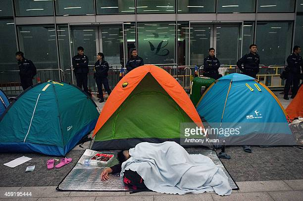 A prodemocracy protester sleeps on the floor outside the Legislative Council building entrance after clashes with police on November 19 2014 in Hong...