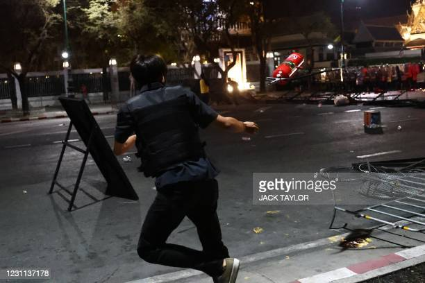 Pro-democracy protester throws a fire extinguisher during a confrontation with riot police at an anti-government demonstration by the Grand Palace in...