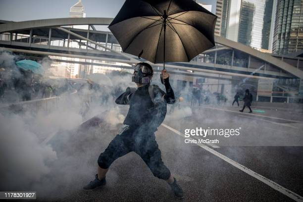 A prodemocracy protester throws a tear gas cannister back at police during clashes outside the Central Government Offices on October 01 2019 in Hong...