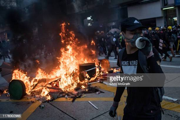 A prodemocracy protester walks in front of a burning barricade during clashes with police in Wan Chai on October 01 2019 in Hong Kong China...
