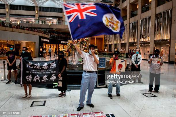 A prodemocracy protester waves a British colonial flag during a Lunch With You rally at a shopping mall in the Central district in Hong Kong on June...