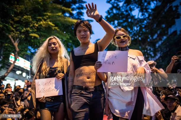Pro-democracy protester wearing a crop top walks down the runway with two female protesters during a fashion show performance at an anti-government...