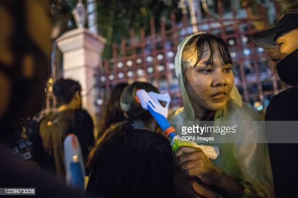 Pro-democracy protester wearing a raincoat and holding a water gun in front of the Royal Thai Police Headquarter during an anti-government...