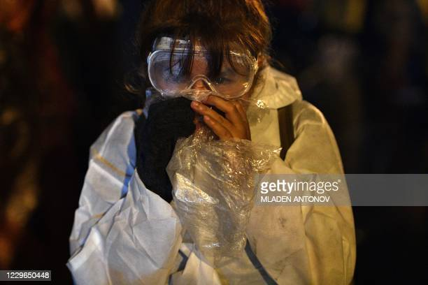 A prodemocracy protester wearing goggles breathes into a plastic bag as tear gas and chemicallaced water cannons are used during an antigovernment...