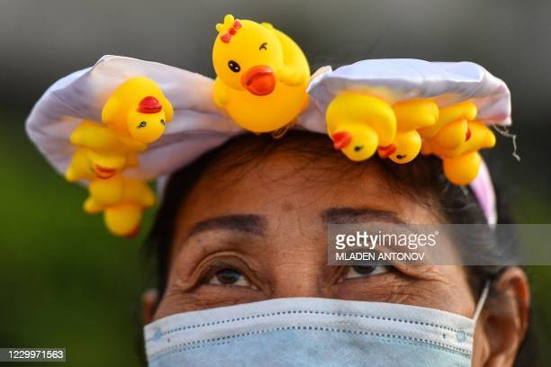 Pro-democracy protester wears a hairband featuring small yellow rubber ducks while taking part in an anti-government rally at Wongwian Yai in Bangkok...