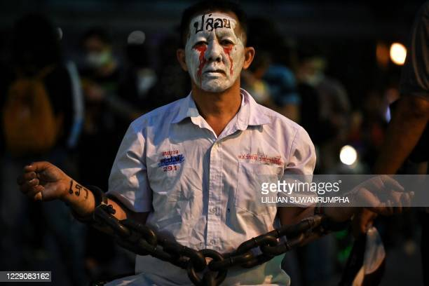 Pro-democracy protester wears chains and make-up during a demonstration at a road intersection in Bangkok on October 15 after Thailand issued an...