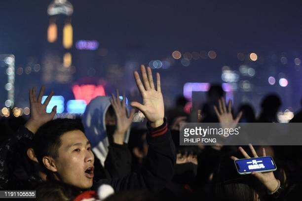 Prodemocracy protesters and people chant slogans and gesture according to the five key demands laid out by protesters in Hong Kong during New Year's...