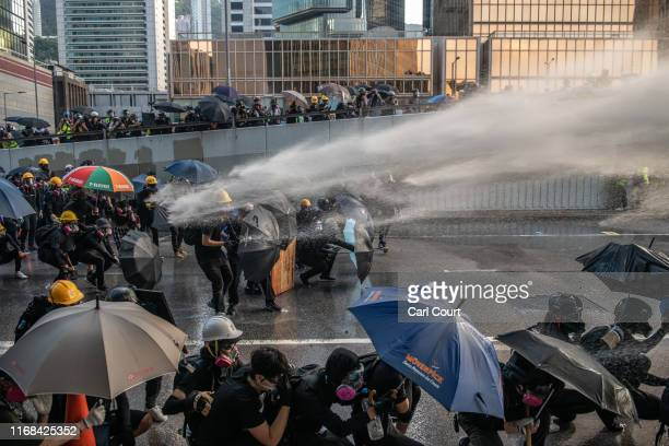 Pro-democracy protesters are hit by a water cannon during clashes at the Central Government Offices on September 15, 2019 in Hong Kong, China....