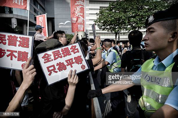 Prodemocracy protesters are prevented by policemen from reaching the venue of a flagraising ceremony during the celebrations of China's national day...
