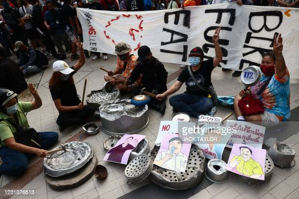 Pro-democracy protesters bang pots and pans as they take part in a rally demanding the end of Thailand's royal defamation law, and to preserve...