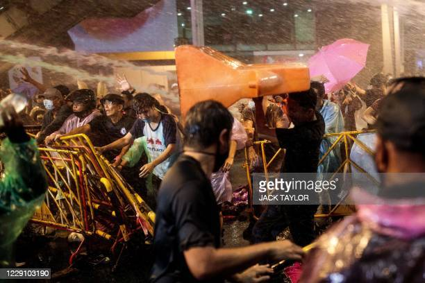 Pro-democracy protesters break through barricades as police use water cannons during an anti-government rally in Bangkok on October 16, 2020.