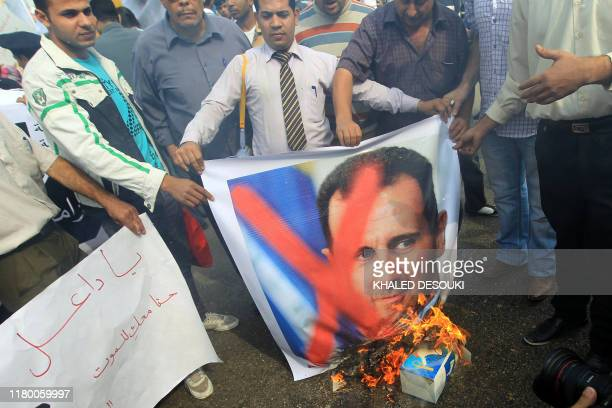 Prodemocracy protesters burn portraits of Syrian President Bashar alAssad during a demonstration outside the Arab League headquarters in Cairo where...