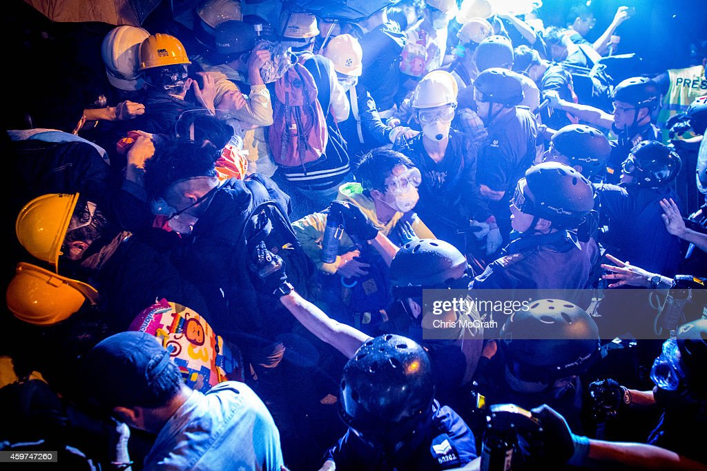 Pro-democracy protesters clash with police as they try to take over Lung Wo Road outside Hong Kong's Government complex on November 30, 2014 in Hong Kong. Leaders from the Federation of Students called on fellow protesters to attend a rally and come prepared for escalated action. Protesters were asked to bring masks, umbrellas and helmets in a bid to move the protests forward after police successfully cleared the Mong Kok protest site earlier this week.