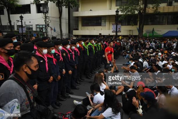 Pro-democracy protesters confront police officers at Ratchaprasong interjection central of Bangkok near Royal Thai Police Headquarter on October 15,...