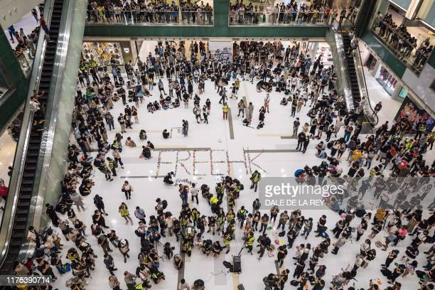 TOPSHOT Prodemocracy protesters gather for a rally at a shopping mall in the Sha Tin district in Hong Kong on October 12 2019 Hong Kong protesters...
