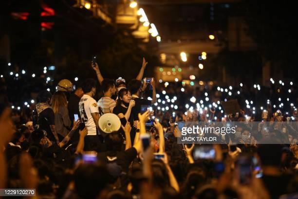 Pro-democracy protesters hol dup their mobile phones during an anti-government rally at Udomsuk in Bangkok on October 17 as they continue to defy an...